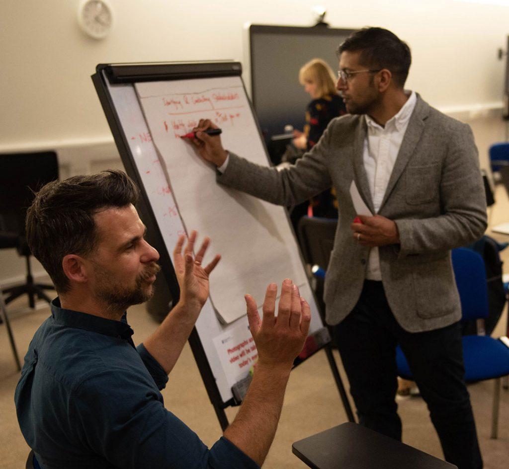 Two men discussing alongside whiteboard